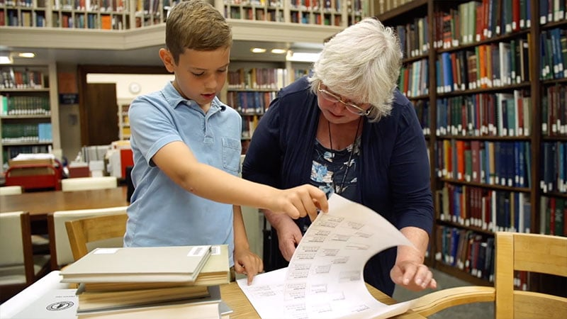 A young student looks over historical documents with a librarian.