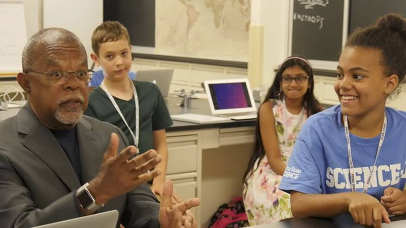Henry Louis Gates, Jr., host of PBSs Finding Your Roots series, talking with several students in a classroom.