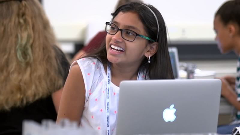 A student smiles in class from behind her laptop.