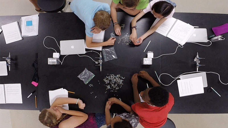 An overhead photograph of a lab table with students 				performing a classifiction exercise with different types of hardware screws.