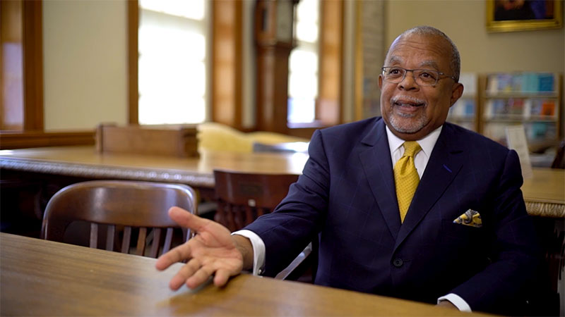 Henry Louis Gates, Jr sitting at a table in suit and yellow tie discussing the Finding Your Roots - The Seedlings project